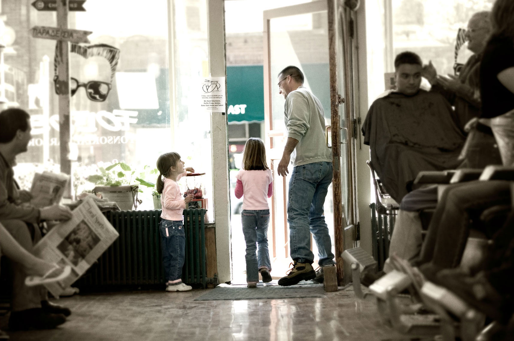 Young family walking out the door of a barber shop