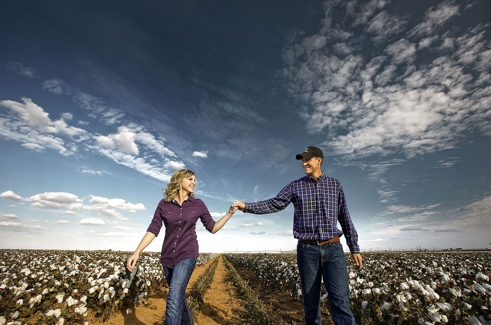 Young newlywed couple walking through cotton.