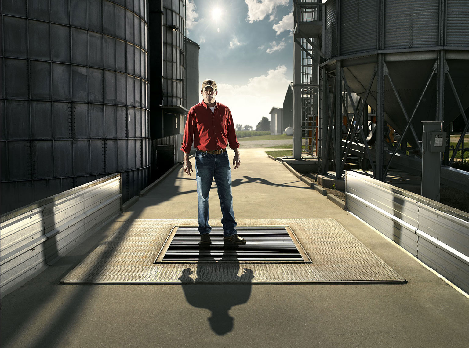 Corn and soybean farmer standing under his grain elevator.