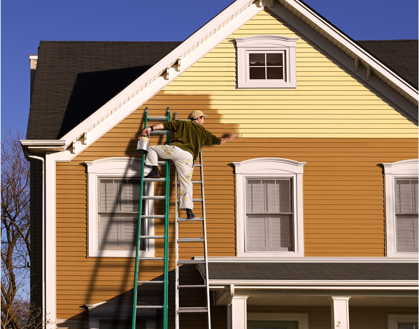 Man on a ladder painting a house