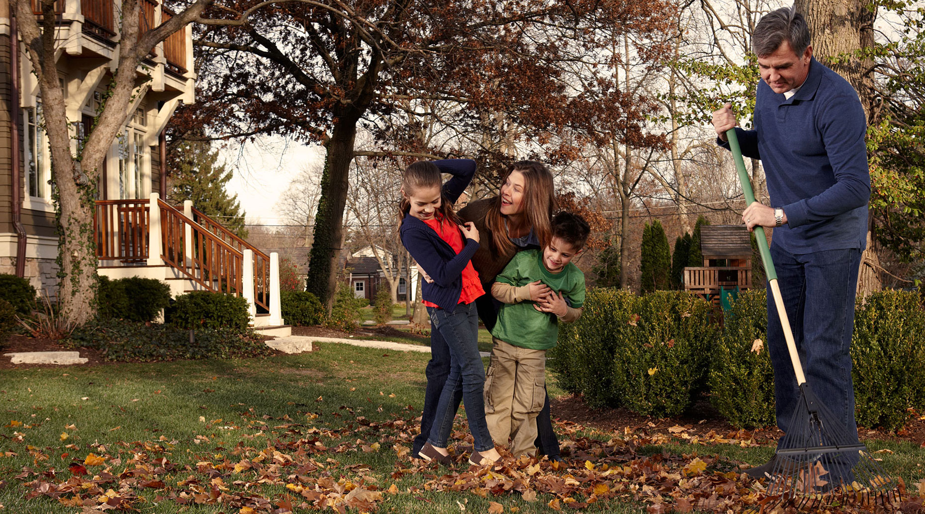 Young family playing in fall leaves.