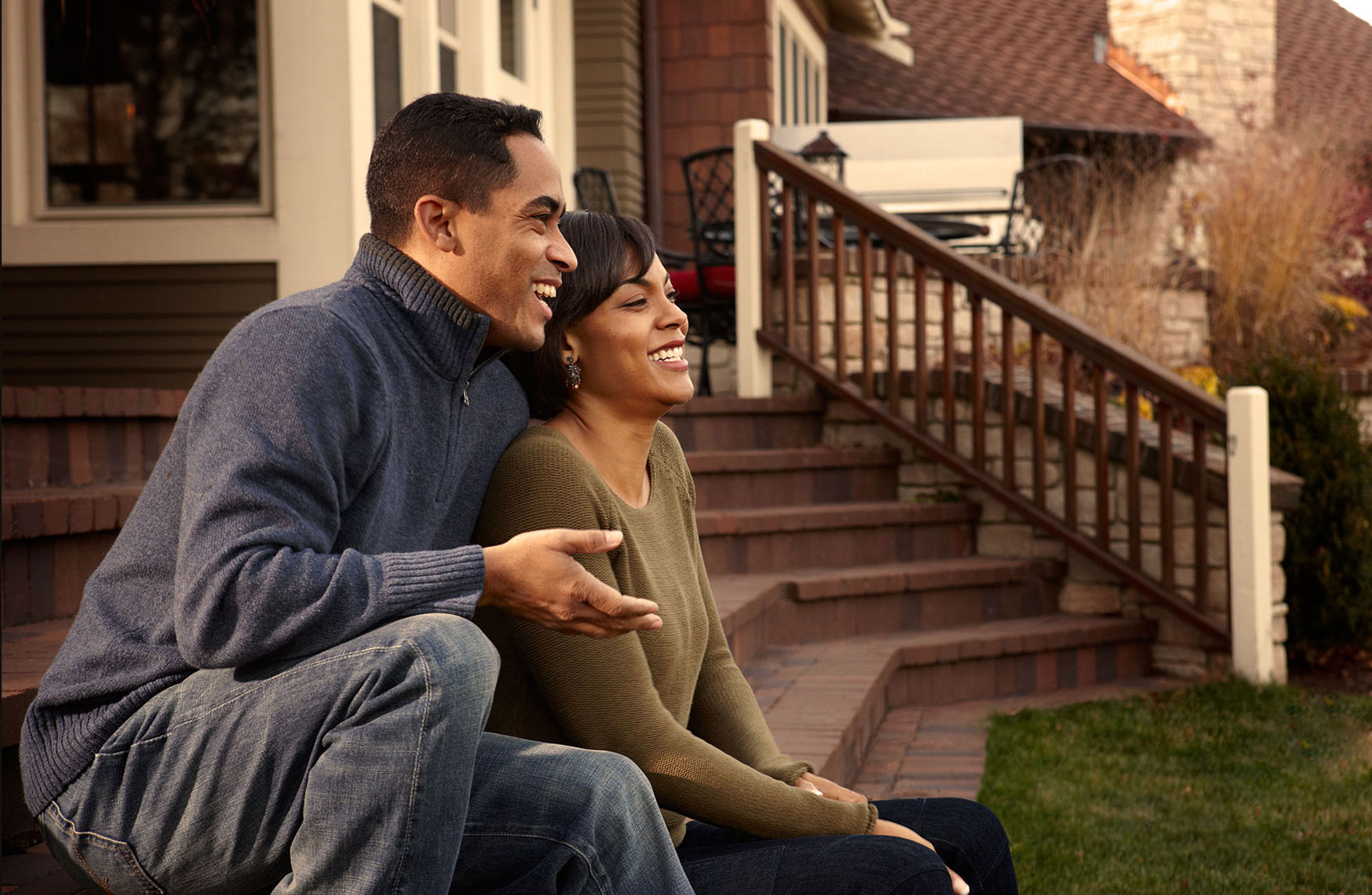Young African American couple sitting on the back yard deck.