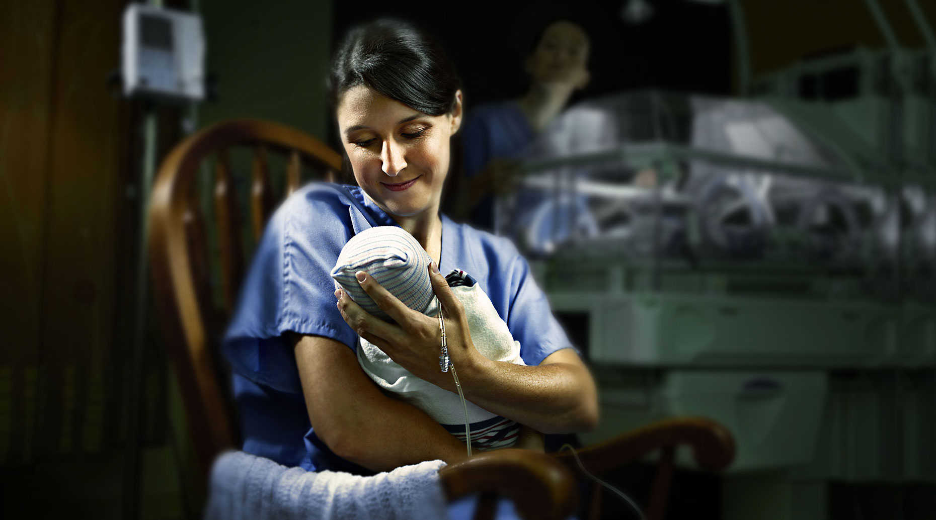 Nurse holding a baby in a hospital room.