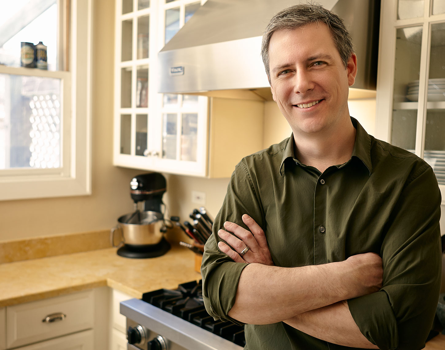Smiling man standing in his kitchen