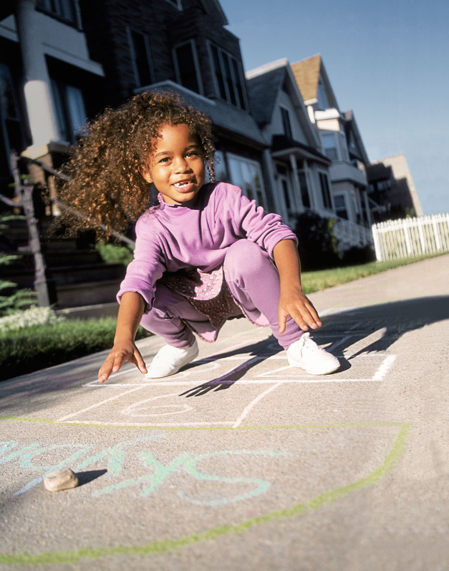 Young girl playing hopscotch.