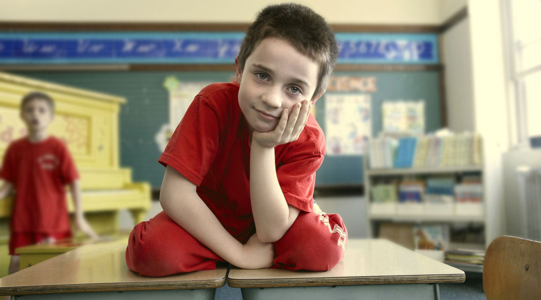 Young boy sitting on top of his desk.