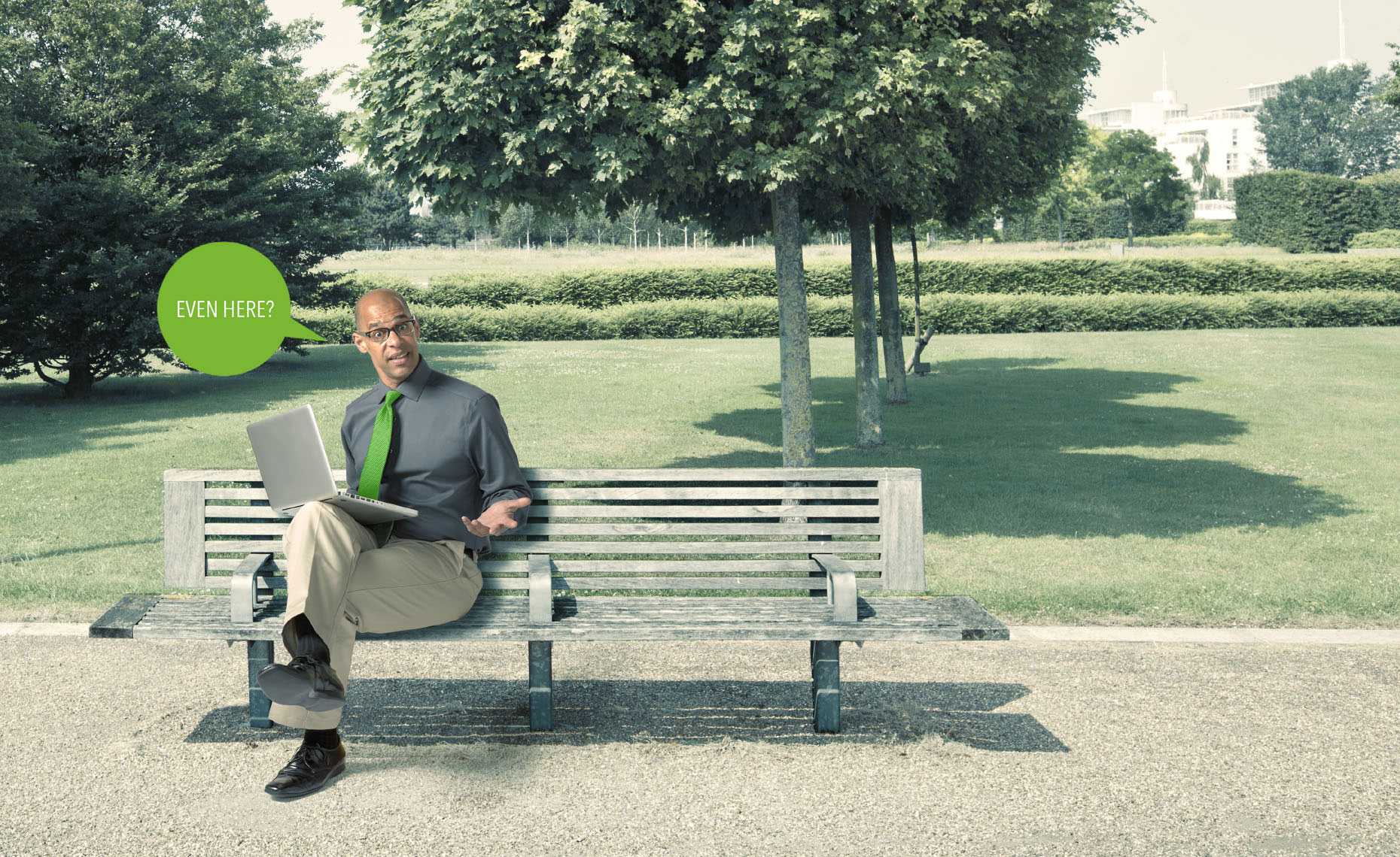 African American man sitting on a park bench holding a laptop