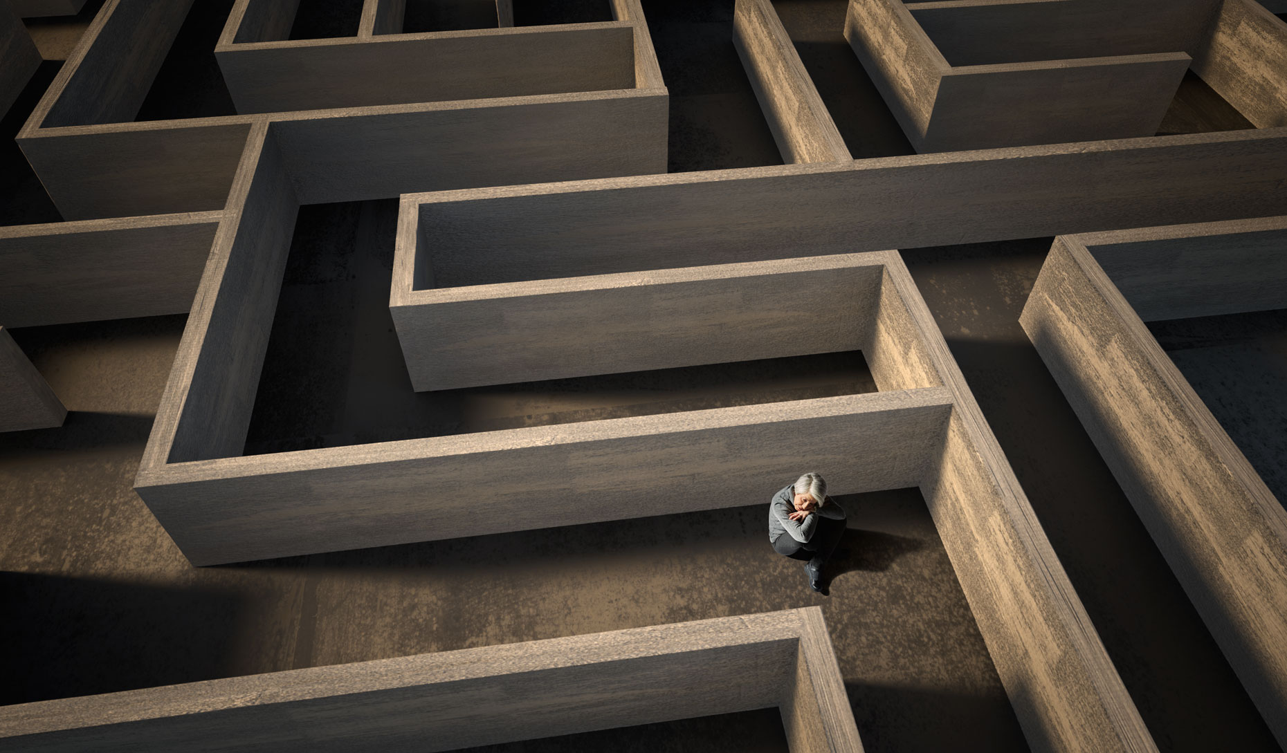 Depressed older woman seated in a maze