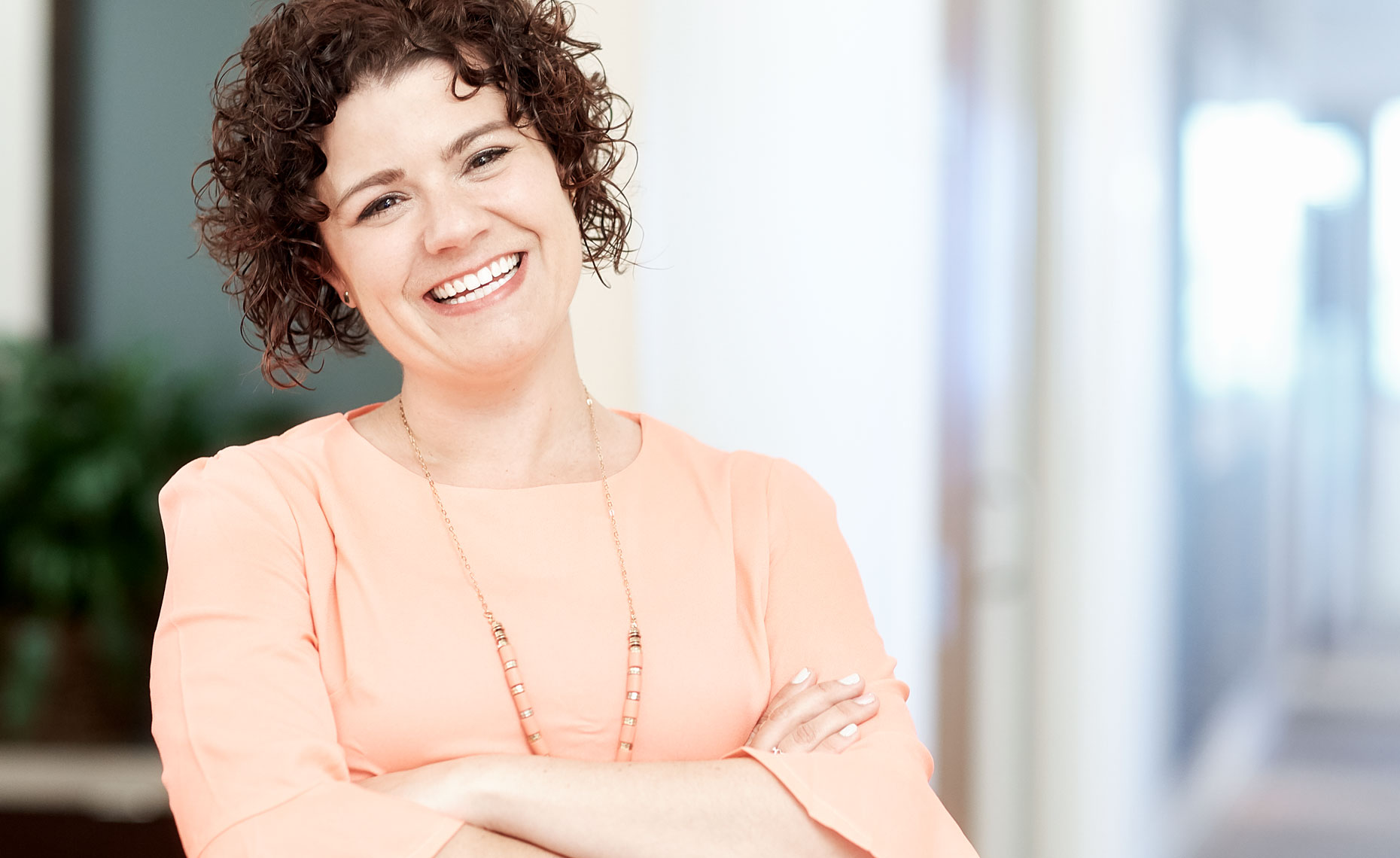 Smiling woman with dark curly hair.