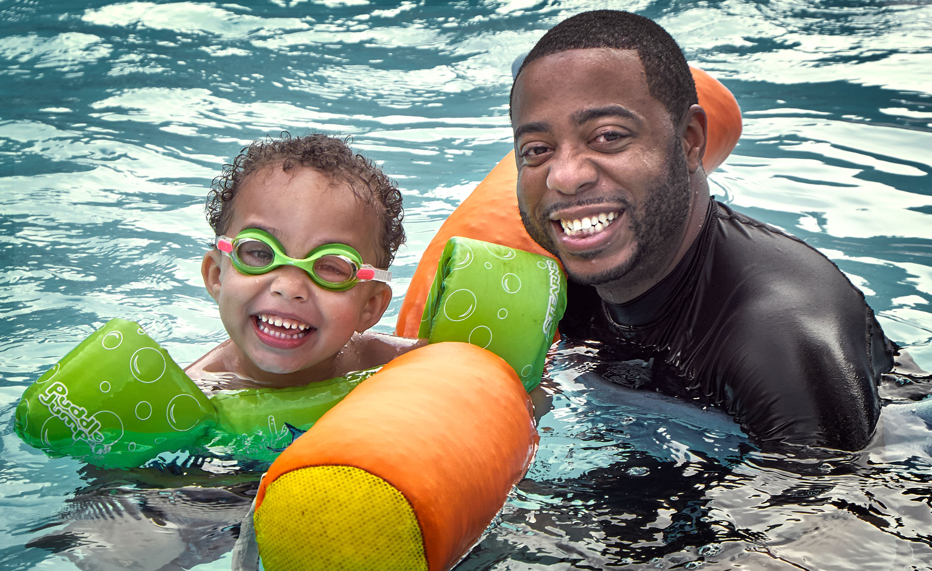 African American father and son playing in a swimming pool