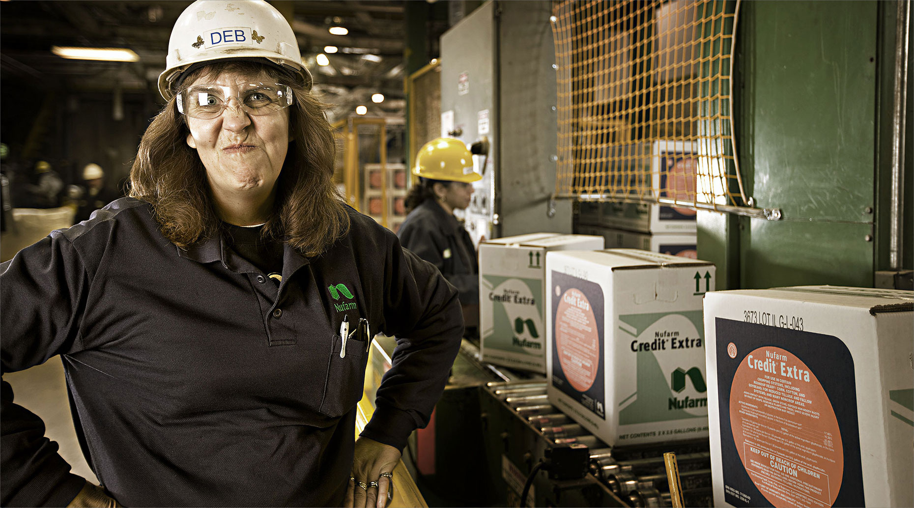 Woman factory worker with hard hat and safety glasses