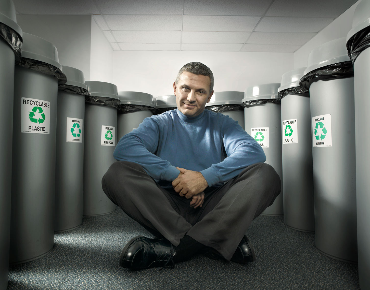 Environmental engineer sitting with recycle bins